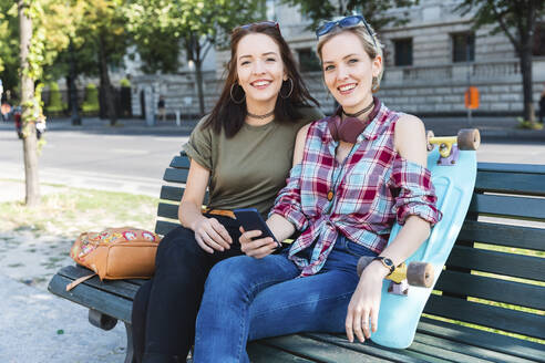 Portrait of two young women sitting on bench with skateboard and mobile phone - WPEF02203