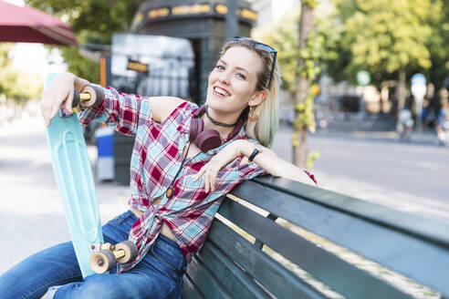 Portrait of smiling young woman sitting on bench with skateboard - WPEF02206