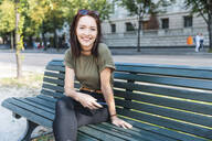 Portrait of smiling young woman sitting on bench with smartphone - WPEF02209