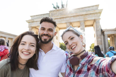 Portrait of three happy friends taking selfie with cell phone in front of Brandenburger Tor, Berlin, Germany - WPEF02215