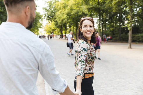 Portrait of happy young woman walking hand in hand with her boyfriend in a park - WPEF02227