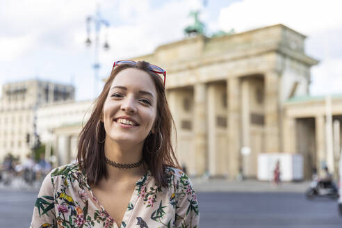 Portrait of smiling young woman in front of Brandenburger Tor, Berlin, Germany - WPEF02236