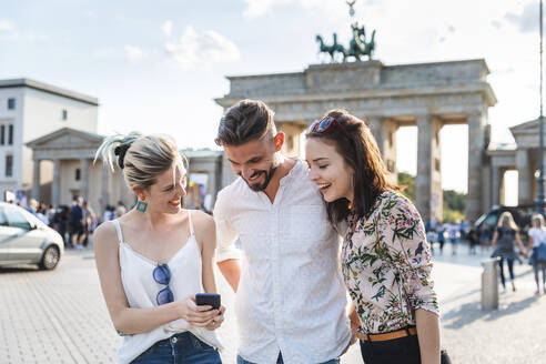 Three friends looking at cell phone in front of Brandenburger Tor, Berlin, Germany - WPEF02239