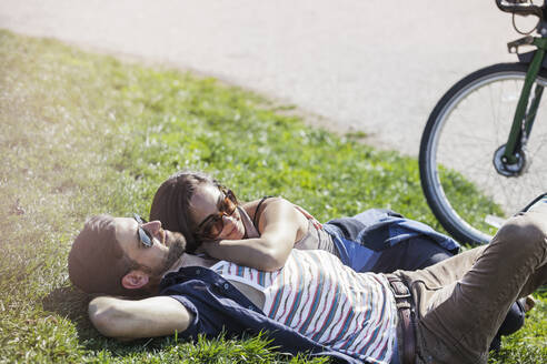 Romantic couple lying on grass at park - CAVF66772