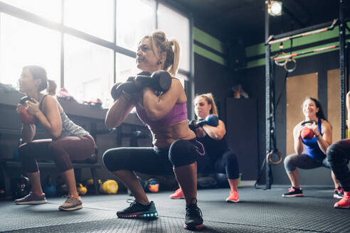 Women training in gym, squatting with kettle bells - CUF52914