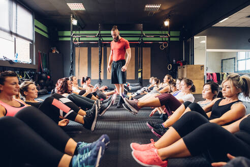 Large group of women training in gym with male trainer, sitting on floor with legs raised - CUF52926
