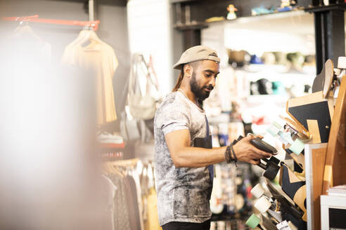 Man choosing skateboard in shop - CUF53100