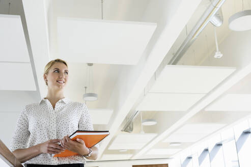 Businesswoman taking break in office corridor - CUF53106