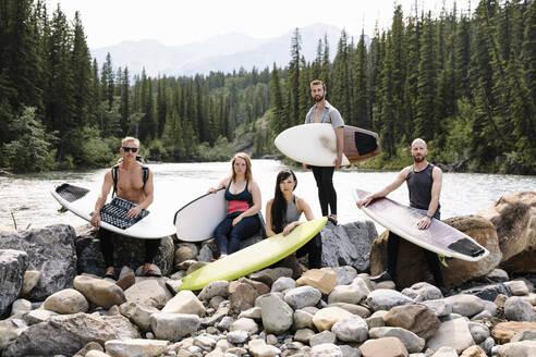 Portrait confident surfer friends with surfboards at riverside - HEROF39666