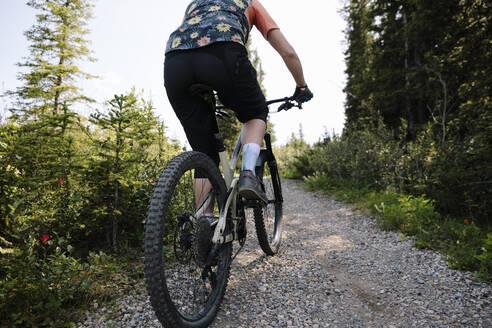 Woman mountain biking on trail in woods - HEROF39744