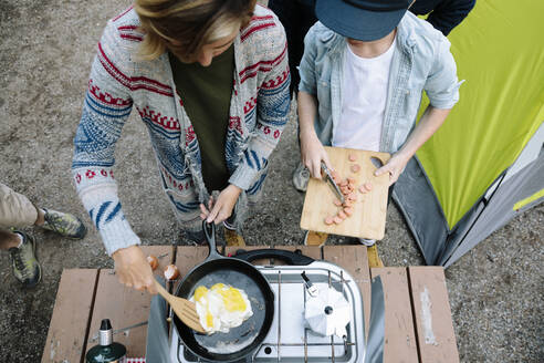Mother and son cooking eggs and hot dogs on camping stove - HEROF39843