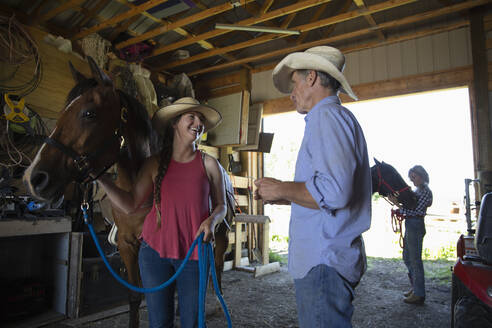Father and daughter standing with horse in stable - HEROF39882