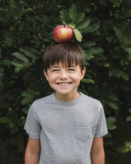 Happy young boy balancing an apple on his head outside by a tree. - CAVF66942