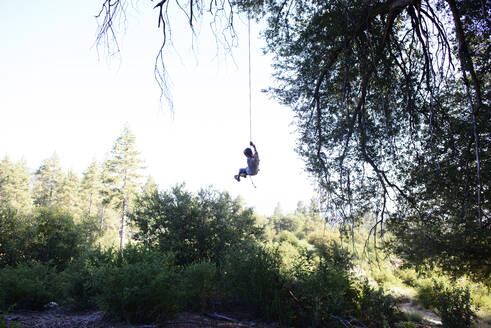 Boy swinging on rope swing at forest against clear sky - CAVF67164