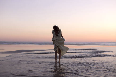 Woman holding dress while standing on shore at beach against clear sky during sunset - CAVF67188