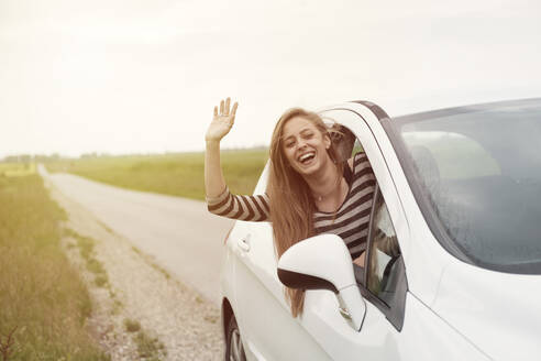 Cheerful young woman waving while peeking from car window on country road - CAVF67416