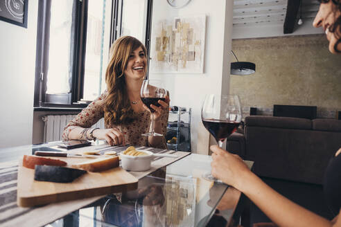 Cheerful woman talking to female friend while holding red wine glass at restaurant table - CAVF67494
