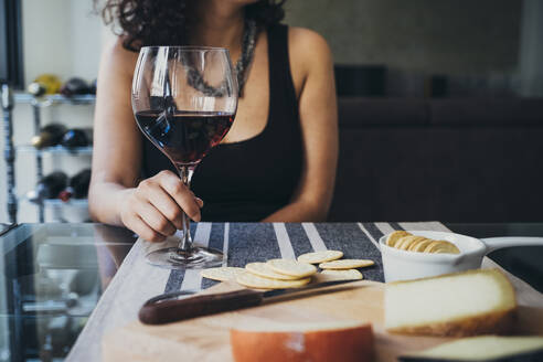 Midsection of woman holding red wine glass at table in restaurant - CAVF67503