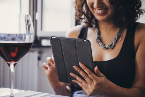 Midsection of young woman using tablet computer at restaurant - CAVF67506