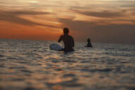 Two surfers in ocean at sunset - CAVF67616