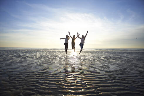 Female friends jumping at beach against sky - CAVF67712
