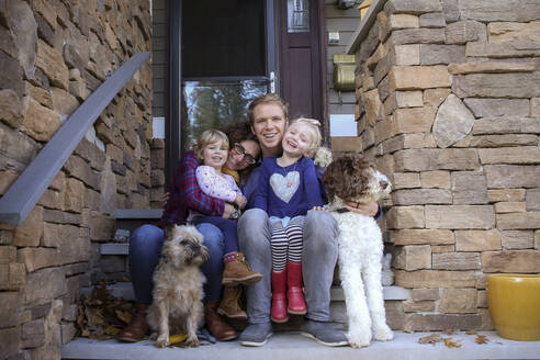 Portrait of happy family with dogs sitting on steps against house - CAVF67760