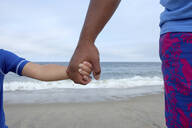 Cropped image of father and son holding hands against sea at beach - CAVF67778