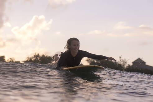 Happy woman lying on surfboard while swimming on sea against sky during sunset - CAVF67893