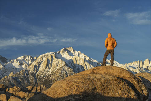 Rear view of man in warm clothing standing on mountain against sky during sunset - CAVF68004