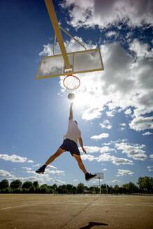 Man playing basketball on yellow court, dunking - OCMF00848