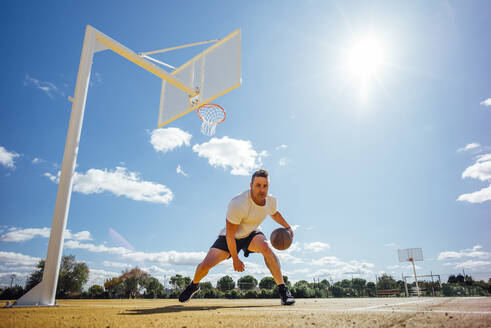 Man playing basketball on yellow court, dribbling - OCMF00851