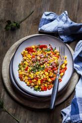 Bowl of warm corn salad with bell pepper, potatoes and diced ham - SBDF04082