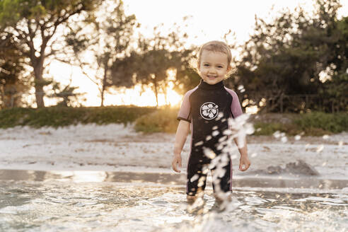 Portrait of cute toddler girl standing in the sea - DIGF08728