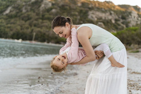 Happy mother carrying her daughter on the beach - DIGF08731