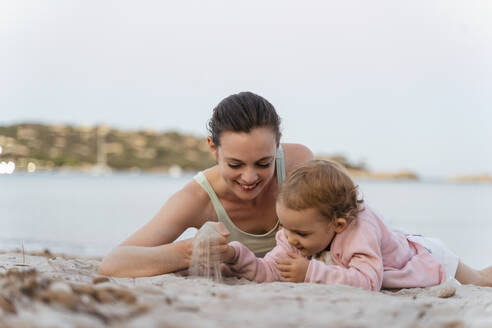 Happy mother and daughter playing with sand on the beach - DIGF08740