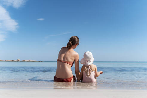 Rear view of mother with daughter sitting in the sea - DIGF08746