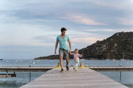 Happy father walking with daughter on a jetty at sunset - DIGF08773