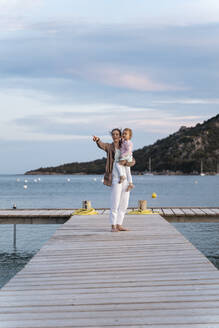 Happy mother carrying daughter on a jetty at sunset - DIGF08776