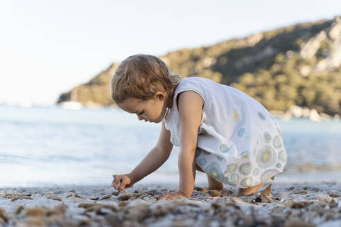 Cute toddler girl playing on the beach - DIGF08794