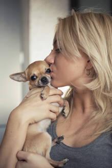 Close-up of teenage girl kissing Chihuahua at home - CAVF68102
