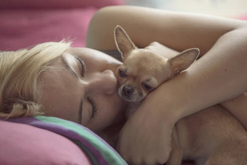 Close-up of teenage girl kissing Chihuahua while lying on bed - CAVF68105
