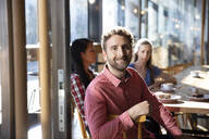 Portrait of smiling man with friends in a cafe - FKF03706