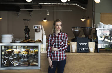 Portrait of confident woman at the counter of a cafe - FKF03709