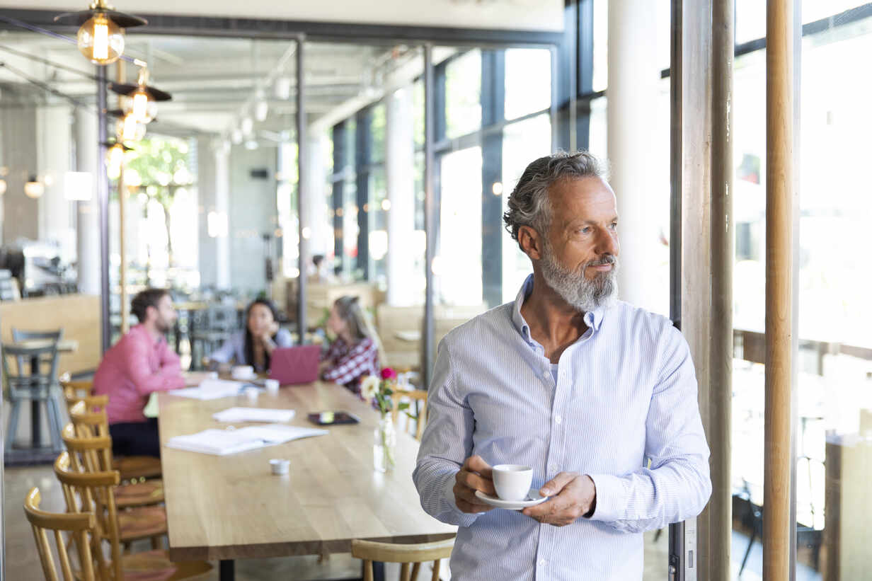 Mature businessman in a cafe with colleagues having a meeting in background - FKF03712 - Florian Küttler/Westend61