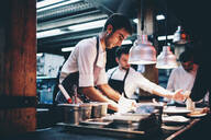 Cook serving food on a plate in the kitchen of a restaurant - OCMF00853