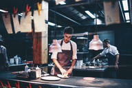 Cook serving food on a plate in the kitchen of a restaurant - OCMF00856