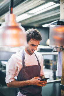 Cook using smartphone in the kitchen of a restaurant - OCMF00865