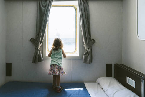 Back view of little girl standing on bed looking to the sea from window of ship's cabin - GEMF03253