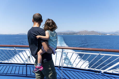 Back view of father and little daughter together on the deck of a ship looking at distance, Mallorca, Spain - GEMF03256