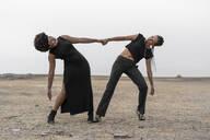Two women dressed in black performing in bleak landscape - ERRF01930